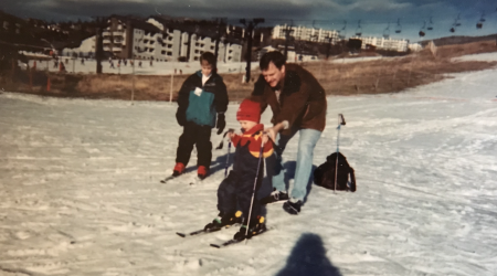 Picture of Nick, his brother, and his father skiing.